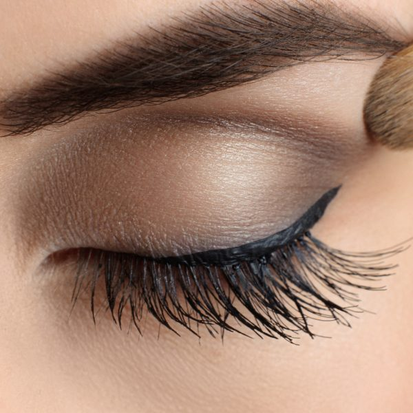 Makeup close-up. Eyebrow makeup, long eyelashes, brush.