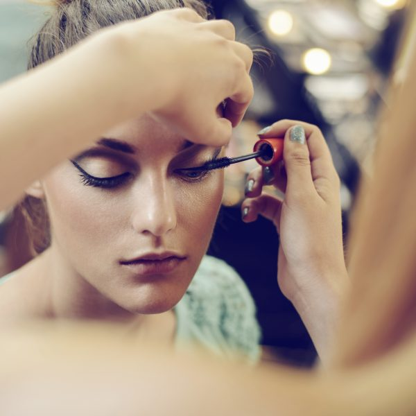 Make-up artist applying the mascara to model. Close up.